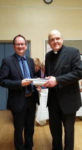 Mark Wardil, Rector's Churchwarden presents Fr Brian with gifts to mark the occasion